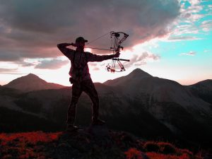 Bow hunter using Huntline Replacement strings while standing on top of a mountain.